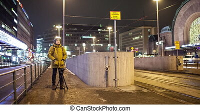 Timelapse of man shooting video in night Helsinki with transport traffic