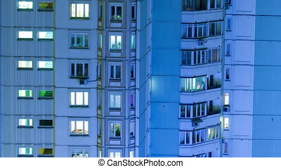 Timelapse of multistorey building with twilnkling lights in late evening