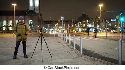 Timelapse of night street with man shooting video. Helsinki, Finland