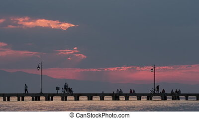 Timelapse of people on pier in the evening