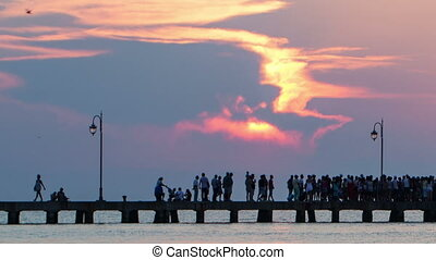 Timelapse of people walking on pier at sunset