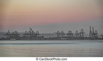 Timelapse of port cranes at dusk - Long shot Timelapse of...