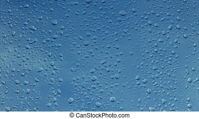 Timelapse of rain water drops on the window glass on blue background with clouds passing by