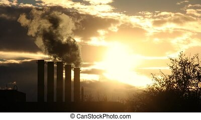Timelapse of smoke from boiler house pipes against winter sunset with sunlight and moving clouds