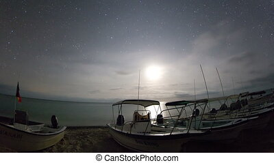 timelapse of stars at night of the ocean and boats in baja california sur, mexico