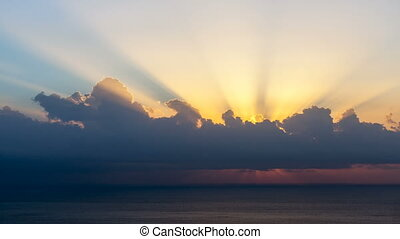 timelapse of sun rays emerging though the clouds at sunrise over sea.