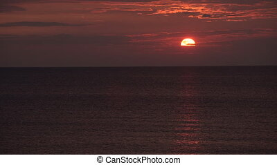 Timelapse of sun setting into the sea. Dramatic sunset sky panorama with burning colourful clouds background. Idyllic seascape backdrop at dawn. Majestic cloud scenery on vacation