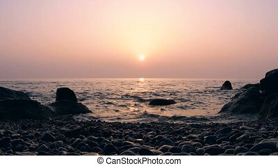 Timelapse of Sunrise Above the Sea with Rocks in Water