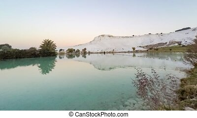 Timelapse of the pond with ducks in front of the white hill named as Cotton Castle. Twilight reflection before the sunrise, Pamukkale, Turkey. 4k