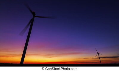 Timelapse of wind turbine for alternative energy on sunset background