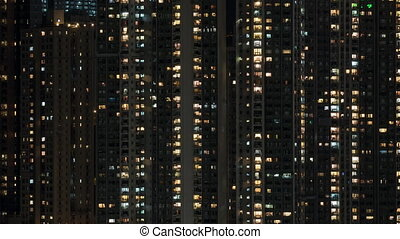 Timelapse of window lights in high-rise apartment block at night