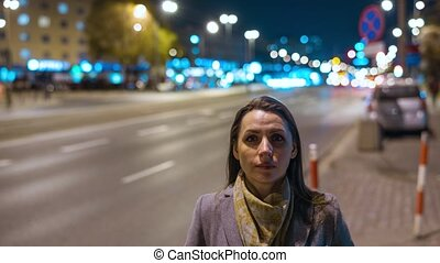 Timelapse of woman standing still on crowded evening street...
