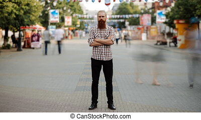 Timelapse of Young bearded man standing still at sidewalk in...