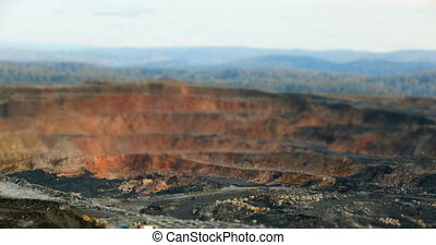 Timelapse Tilt-shift panorama of coal mining quarries, yellow dump trucks carry coal