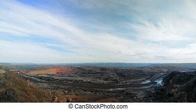 Timelapse panorama of coal mining quarries, dump trucks carry coal