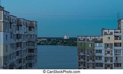 timelapse. the view from the window. white clouds on blue sky. apartment building near the lake