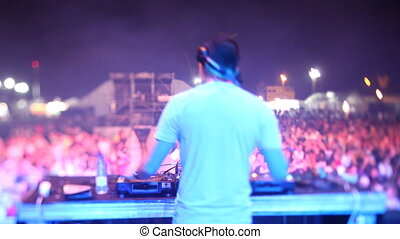 timelapse view from behind a dj looking out to the crowd at a festival