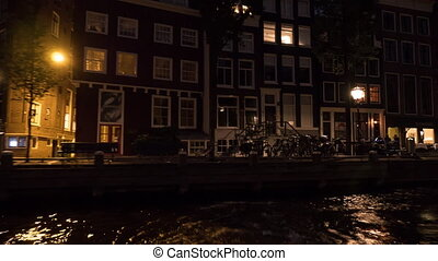Timelapse view of cityscape during river cruise at night, Amsterdam, Netherlands