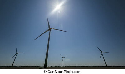 Timelapse Wind Turbines with blue sky and the sun shining