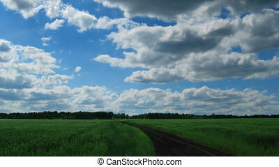 timelapse with clouds moving to you over green field with track