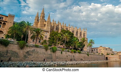 Timelapse with flying clouds over Cathedral of Palma de Mallorca and Almudaina Castle