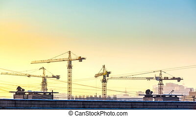 silhouette of cranes working on construction site on sunset...