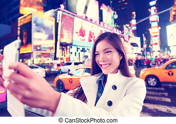 Times Square tourist taking selfie with tablet app
