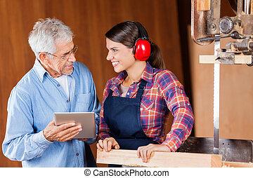 timmerman, gebruik, digitaal tablet, terwijl, kijken naar, collega
