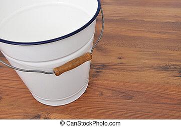Tin bucket on wood