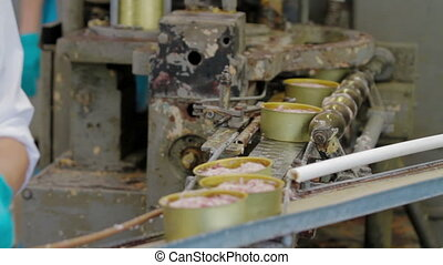 tin cans with meat being sealed and tightened by a factory machine