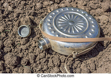 Tin flask on dry ground