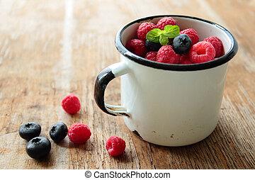 Tin mug with fresh fruits of raspberries and blueberries