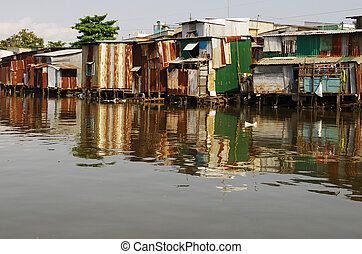 Tin shacks along a river, almost collapsing