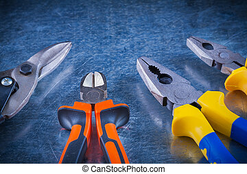 Tin snips pliers nippers on scratched vintage metallic surface horizontal version construction concept.