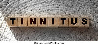 TINNITUS word written on wood block. TINNITUS text on wooden table for your desing,. Healthcare concept