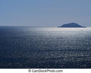 Tino island near Portovenere, Liguria. Sunlight sparkles on the silver sea. Idyllic, with small boat.