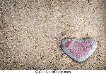 A grey heart shaped stone on grainy sand, tinted with a red heart. This version is vignetted and edited to give a retro or lo-fi appearance.