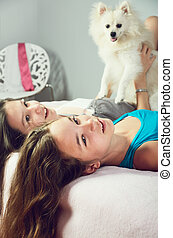 tinted image two girls with a Pomeranian lay on the bed and...