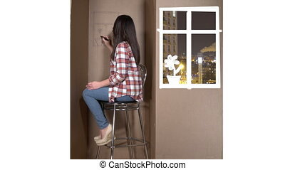 Tiny apartment in a cardboard box woman drawing flower on a wall