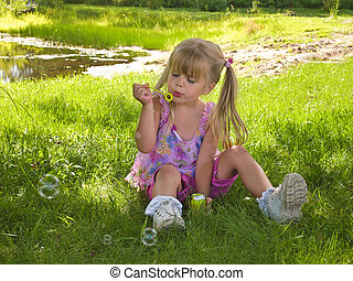 Little girl in pigtails blowing bubbles.