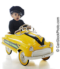 Tiny Cabbie - A toddler cab driver wering a cabbie hat and...