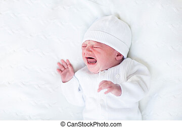 Tiny crying newborn baby ni a white knitted hat and jacket