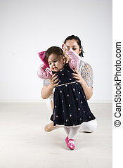 Tiny dancer - Young mother holding her little girl helping...