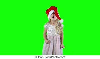 Tiny girl puts on a Christmas hat and playing naughty. green...
