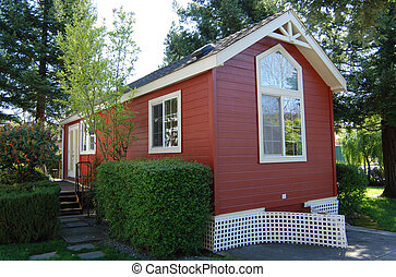 Small, tiny red house situated amongst trees. Small eco footprint