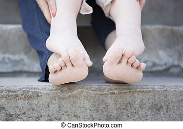 Tiny legs of child and his mother