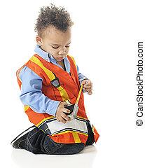 Tiny Measuring Construction Worker - A biracial preschooler...