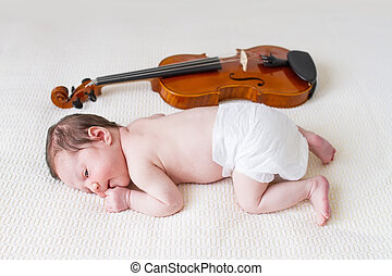 Tiny newborn girl lying next to a violin