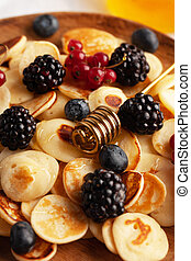 Tiny pancakes with berries, honey close-up on a wooden plate. Pancake cereal. concept of Breakfast, food trends.