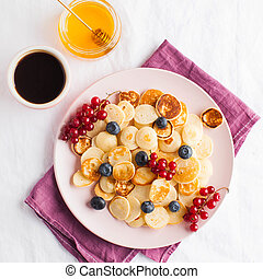 Tiny pancakes with berries, honey, coffee. Pancake cereal. The concept of Breakfast, food trends. Copy space.